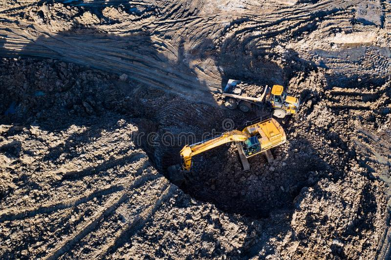 Flyg- surrsikt av grävskopan som laddar person som ger drickslastbilen royaltyfri foto