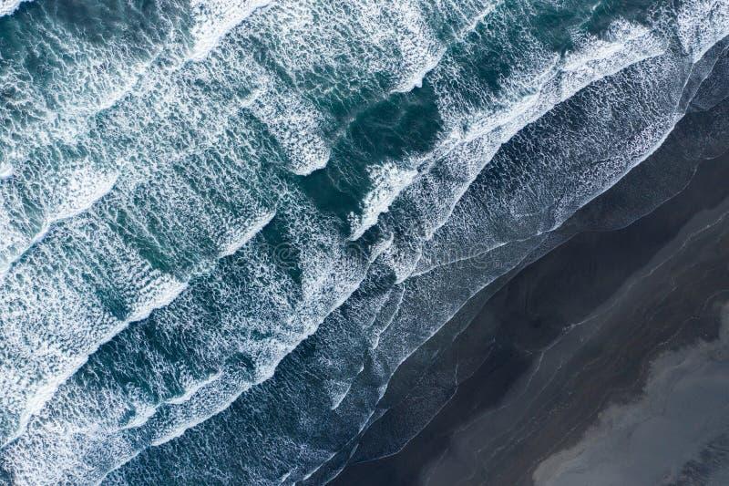 Flyg- surrsikt av havvågor som tvättar den svarta sandstranden, Island arkivfoto