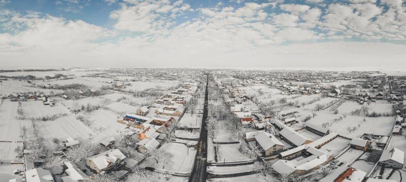 Flyg- surrsikt av stadvägar och hus som täckas med snö på molnig solig dag för vinter royaltyfri bild