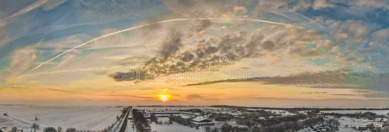 Flyg- surrsikt av stadvägar och hus som täckas med snö på molnig solnedgång arkivbild