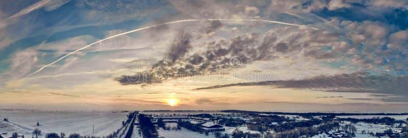 Flyg- surrsikt av stadvägar och hus som täckas med snö på molnig solnedgång royaltyfri bild