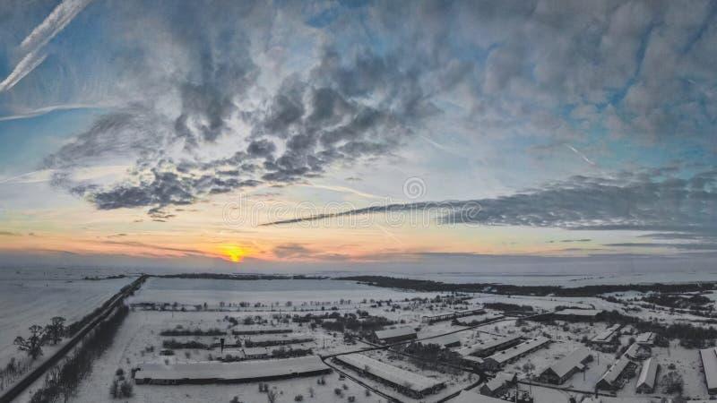 Flyg- surrsikt av stadvägar och hus som täckas med snö på molnig solnedgång arkivfoto