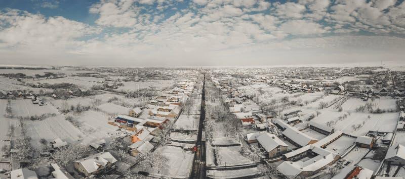 Flyg- surrsikt av stadvägar och hus som täckas med snö på solig dag för vinter arkivfoto