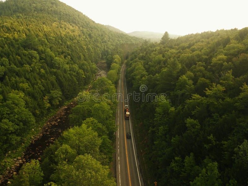 Flyg- surrskott av lastbilen som kör ner en väg i de dimmiga Adirondack bergen arkivbilder