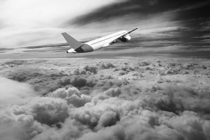 Flyg till och med moln, moln som ses från ett flygplan, solsken, vit för jordbakgrundssvart arkivfoton