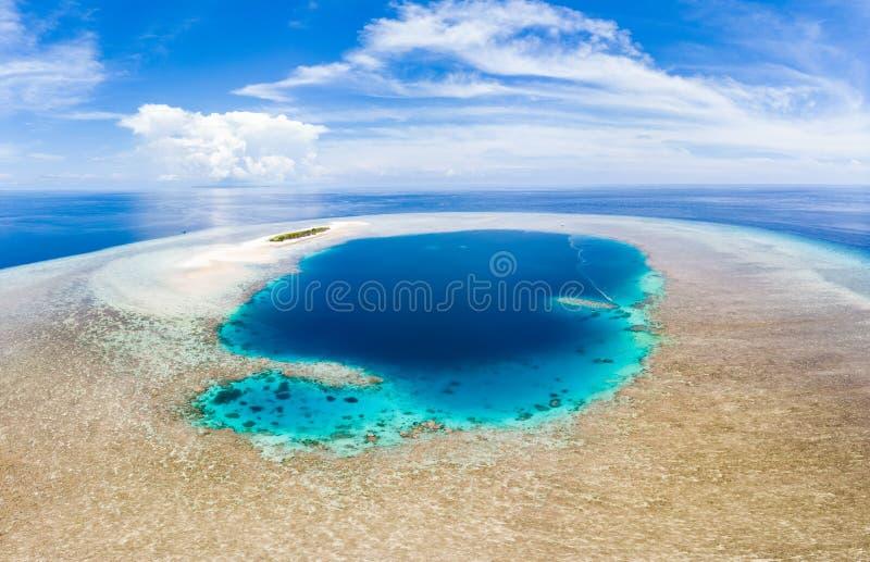 Flyg-: tropisk atollsikt fr?n den ovann?mnda bl?a reven f?r korall f?r lagunturkosvatten, Wakatobi Marine National Park, Indonesi royaltyfria foton