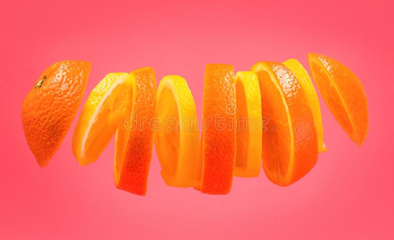 Flyga apelsiner och citronskivor på rosa bakgrund Skivad apelsin- och citroncitrus som isoleras på rosa bakgrund Lättfärdighetfru arkivfoto