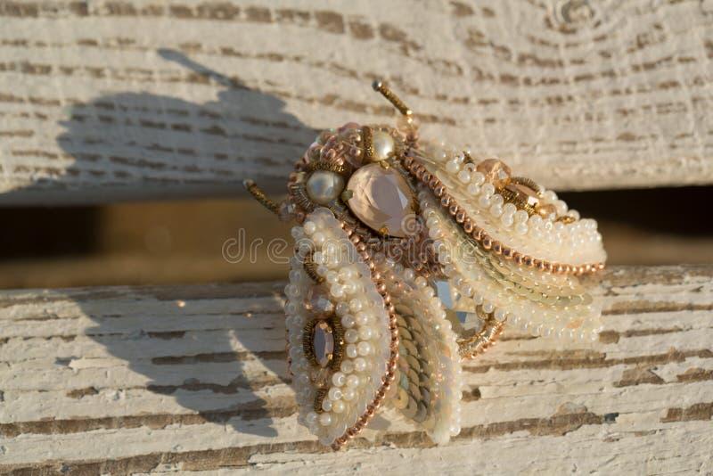 Flyga broschsmycken som göras av pärlor Modetrend av smycken Skönhet och mode av den handgjorda kryptillbehören lyx royaltyfri bild