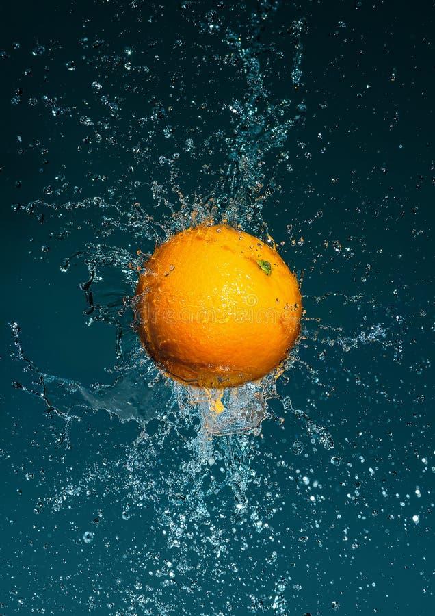 Flyga den mogna apelsinen i vattenfärgstänk fotografering för bildbyråer