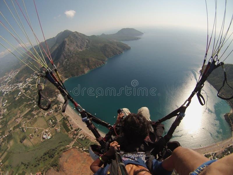 Flyga i himlen ovanför den laguna Paraglidingtandemcykeln royaltyfria foton