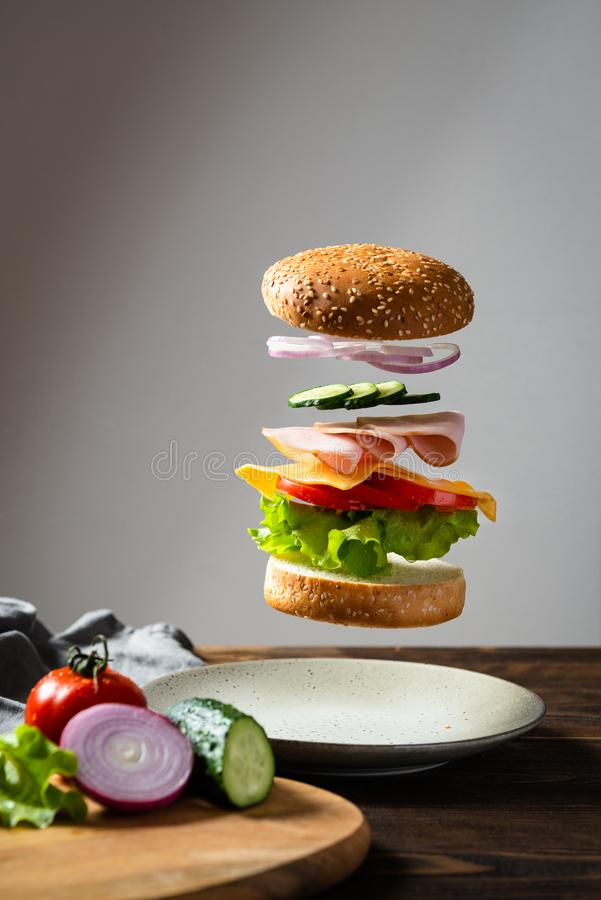 Flyga ingredienser hamburgare eller ostburgare ovanför plattan med ingredienser på träskärbräda på en mörk bakgrund hamburgare royaltyfri bild