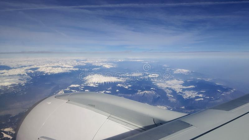 Flyga och resa utomlands, sikt för fågelöga från flygplanfönster på strålvingen på molnig för isbergberg för blå himmel morgon om royaltyfri fotografi