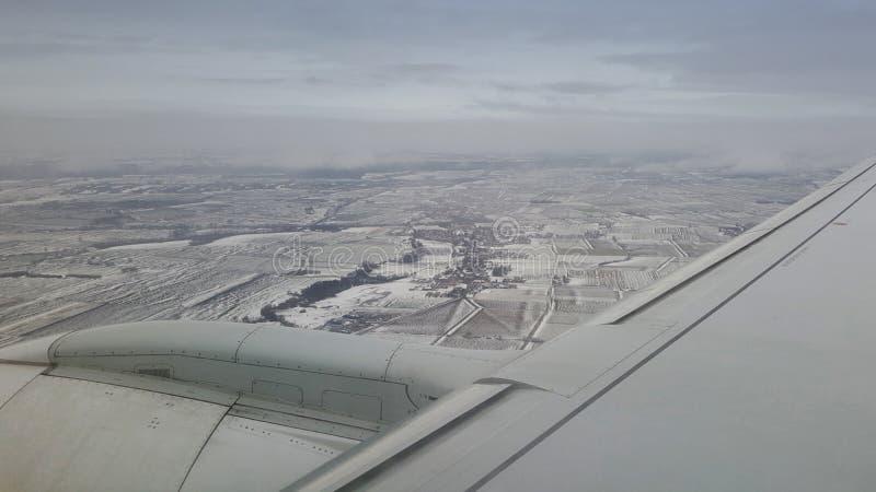 Flyga och resa utomlands, sikt för fågelöga från flygplanfönster på strålvingen på molnigt för isbergberg för blå himmel fält för arkivbild