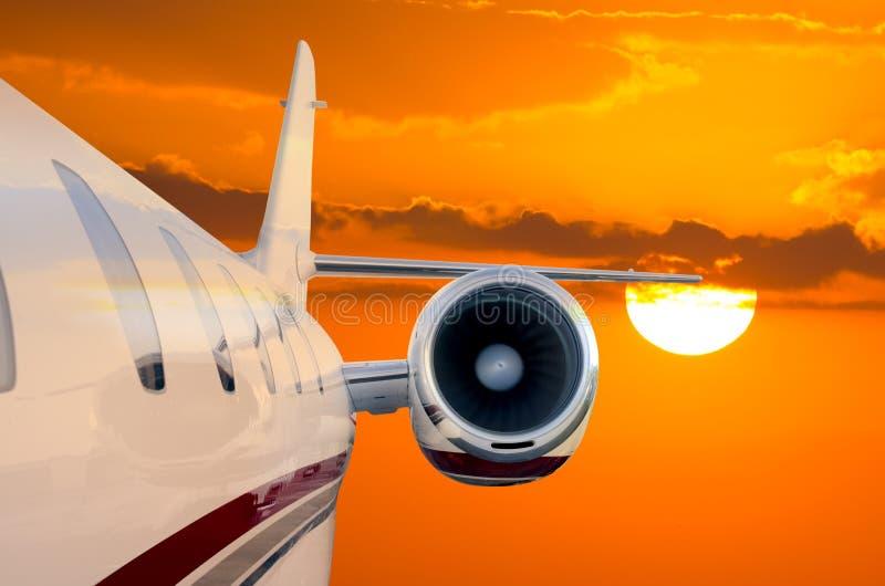 Flyga privata Jet Airplane med solnedgångbakgrund arkivfoto