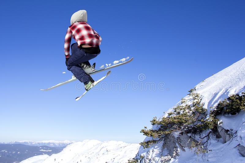 Flyga skidåkaren på hoppinhigh på berg royaltyfri foto