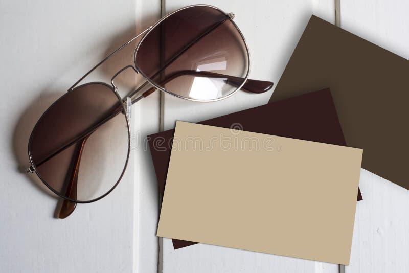 Flygaresolglasögon med tomma bruna affärskort royaltyfria bilder