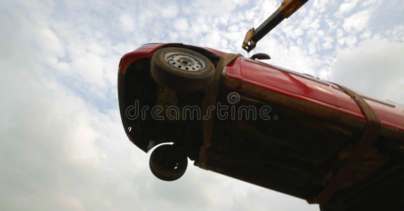 Flygbil som bogserar den skadade bilen över en bärgningsbil, skott för låg vinkel arkivbilder