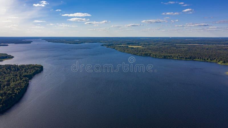 Flygbild av den stora sjön i skogen med stackmolnmoln royaltyfri fotografi