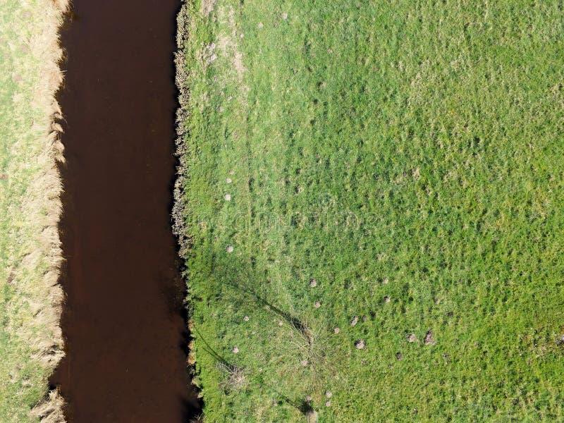 Flygbild av en liten flod vid ängar, abstrakt foto royaltyfri foto