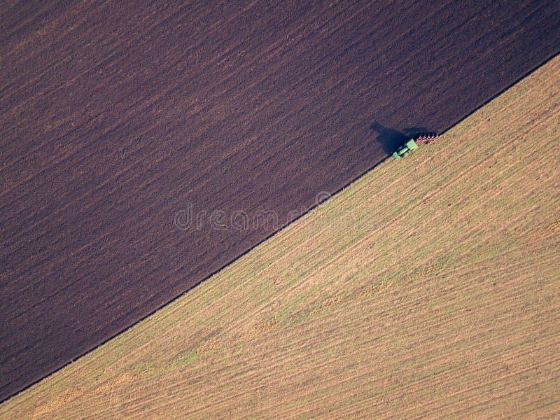 Flygbild av en traktor som plöjer ett fält i en bygd arkivfoton
