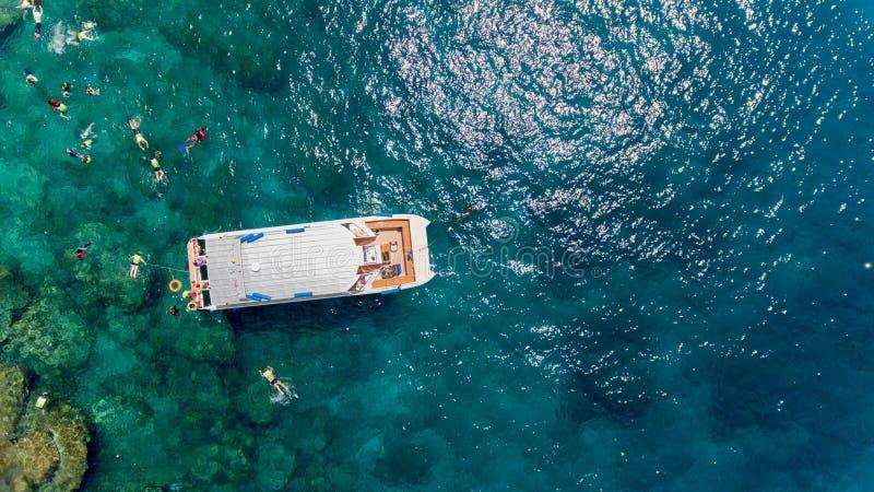 Flygbild av folk som snorklar i tropisk korallrev royaltyfri fotografi