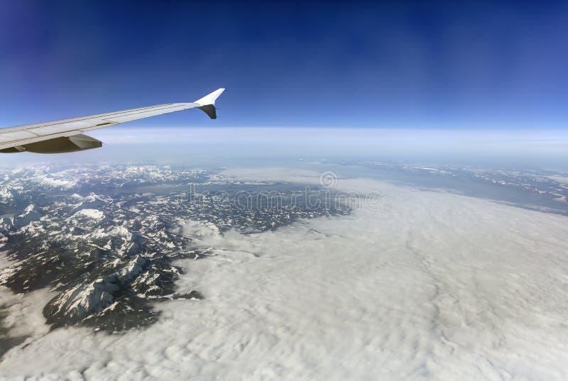 Flygbild av landskapet med moln, snöig berg och sikten som hela vägen sträcker till horisonten arkivfoto