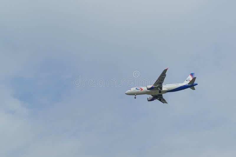 Flygbolag för flygbuss A320-214 Ural för flygplanvitblått med ett fällt ned chassi på himmelbakgrunden royaltyfri fotografi