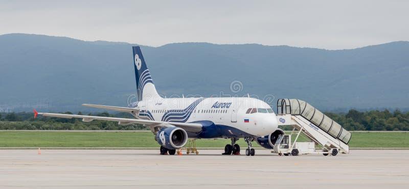 Flygbuss A319 för passagerarestrålflygplan av Aurora Airlines på flygfältet i molnig dag Den mobila stegen är nära med nivån arkivbild