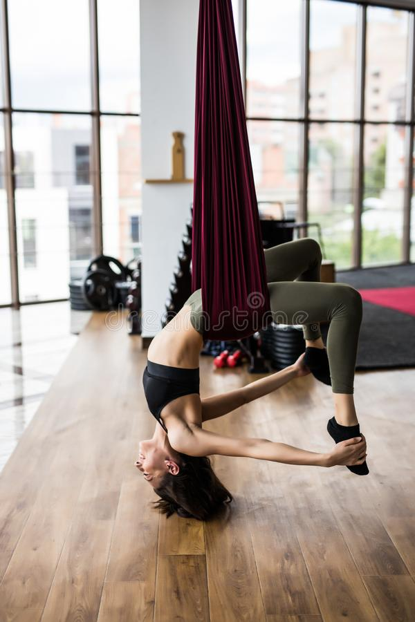 Flyger den slanka konditionkvinnan för ung skönhet att göra yogaövningar i yogastudio royaltyfria bilder