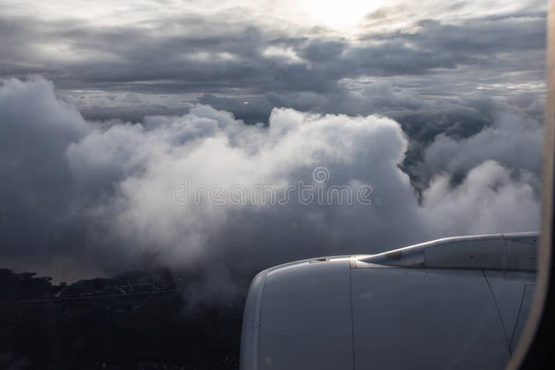 Flyget till och med molnen, nedanför jorden, solen skiner till och med molnen Jetmotorflygplan royaltyfria foton