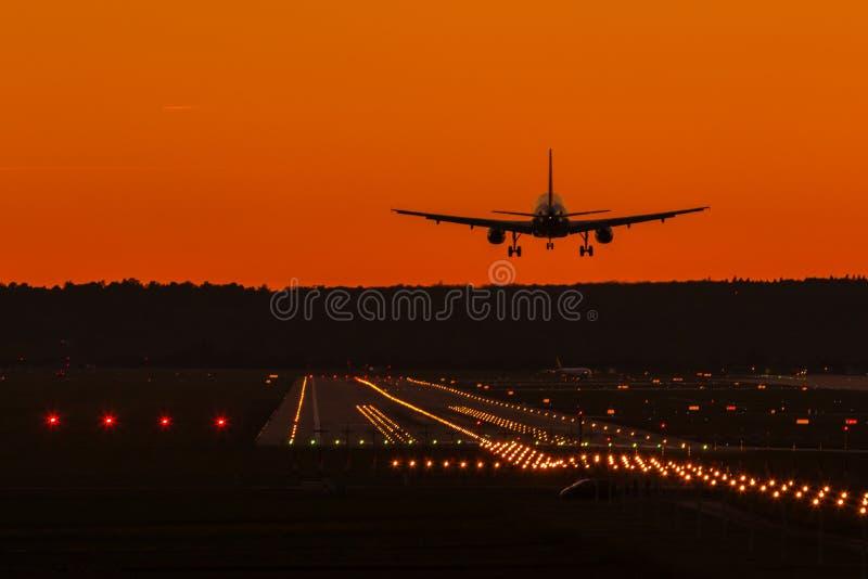 Flygflygplan som får klart att landa i solnedgången royaltyfri fotografi