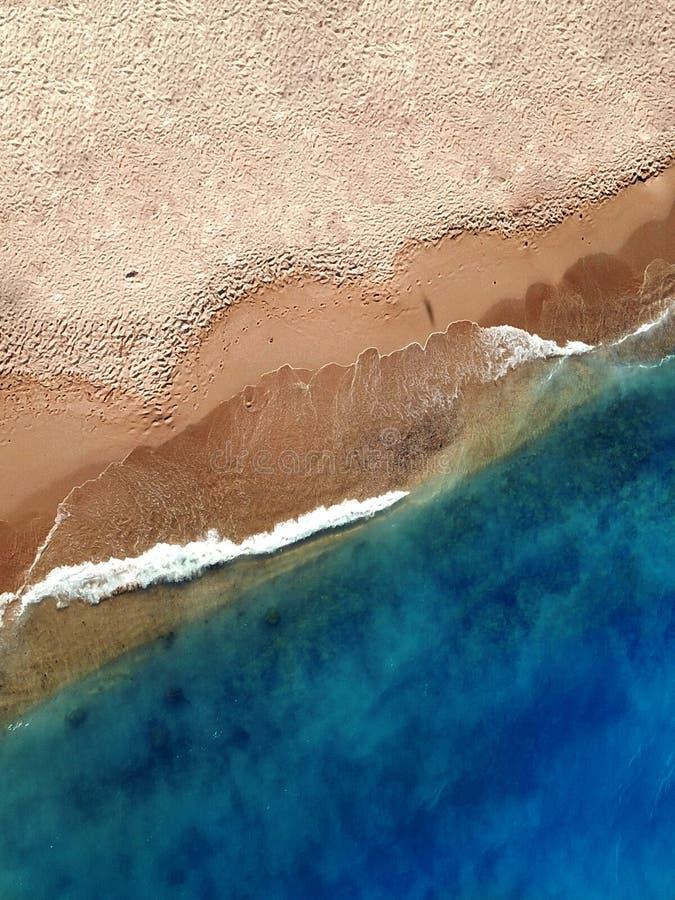 Flygfoto av ett häpnadsväckande exotiskt sandströ nära en blå sjösida royaltyfria foton