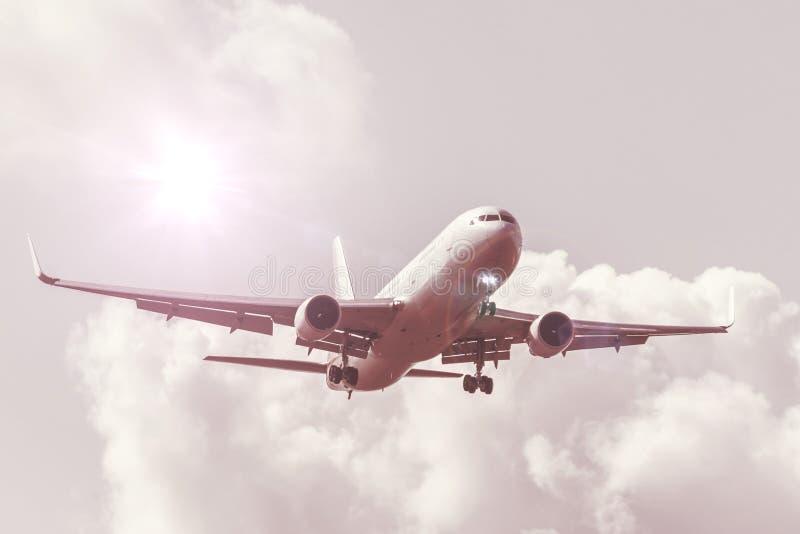 Flyghimmel med moln och sol med en varm skuggning, reflekterat ljus, stort passagerarflygplan som landar på flygplatsen royaltyfria foton