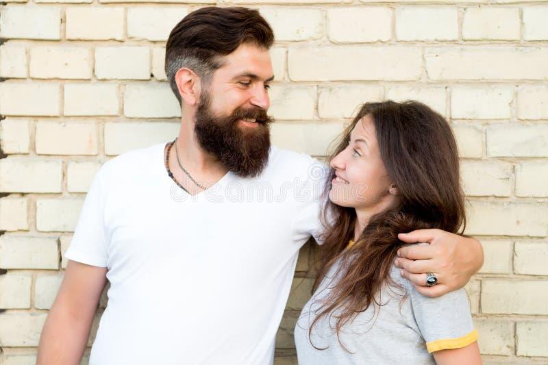 flyghj?rtor ?lskar den mycket r?da skyen dig Sinnliga par som är förälskade på tegelstenväggen Skäggig man som kramar den nätta k royaltyfri fotografi