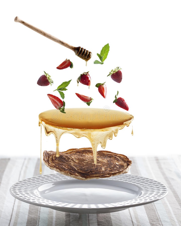 Flygpannkakor med jordgubbar, mintkaramellen och honung royaltyfri bild