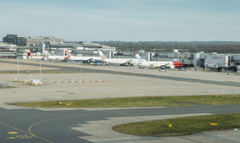 Flygplan av olika trafikflygplan på grov asfaltbeläggning som väntar på passagerare a arkivbild