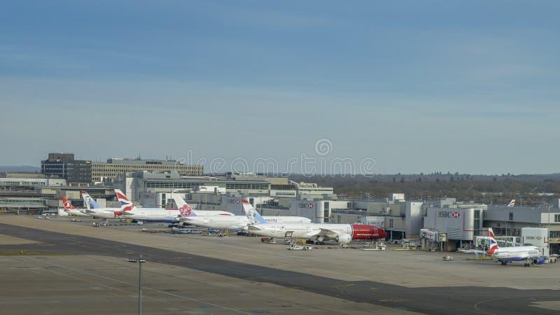 Flygplan av olika trafikflygplan på grov asfaltbeläggning som väntar på passagerare på den norr terminalen för London Gatwick ` s arkivbilder
