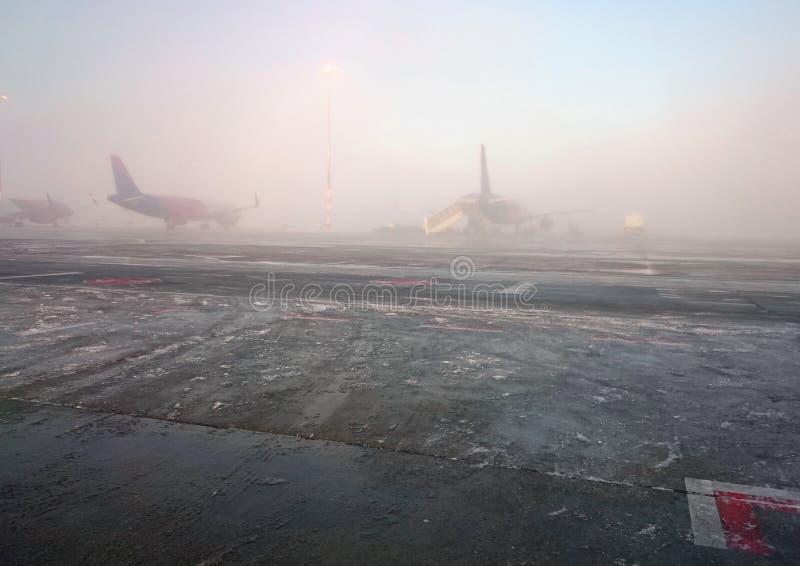 Flygplan får klara att flyga på dimmig morgon Bilden av den dimmiga morgonen på flygplatsen taked vid mobiltelefonen arkivfoto