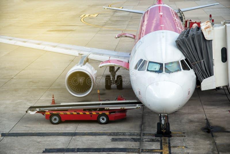 Flygplan i flygplatsen som servas av jordbes?ttningen P?fyllningslast in i flygplanet f?r avvikelse F?rberedelse av flygplanet arkivfoto