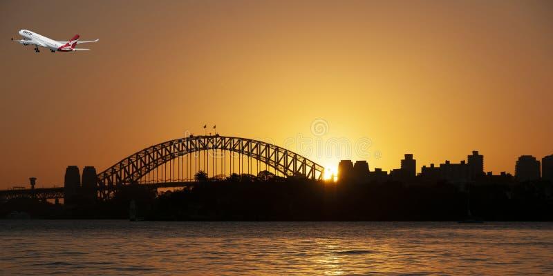 Flygplan i flykten som avgår Sydney i en orange solnedgånghimmel fotografering för bildbyråer