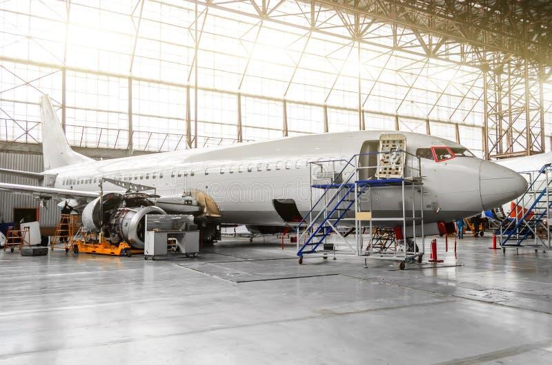 Flygplan i hangaren i underhållet av plätering, inre, motorreparation royaltyfria bilder