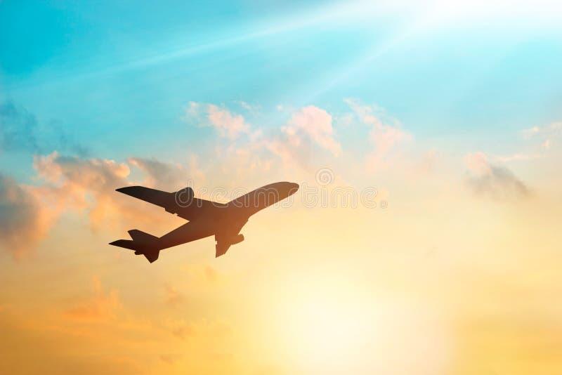 Flygplan i himlen och molnet på solnedgången royaltyfri fotografi