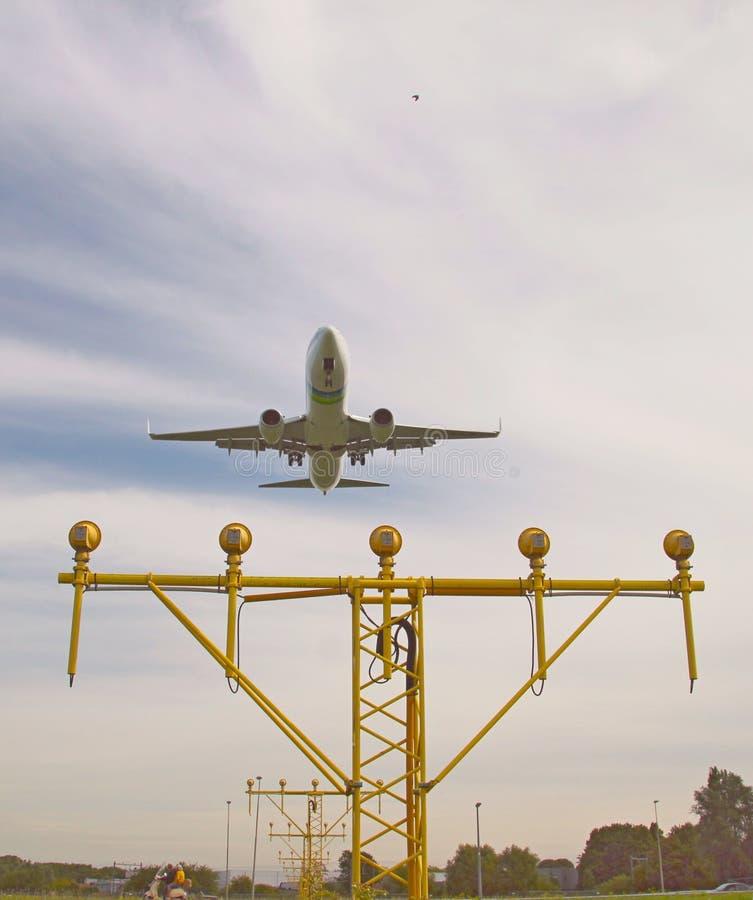 Flygplan landar på den Rotterdam Haag flygplatsen över landningljusen royaltyfri bild