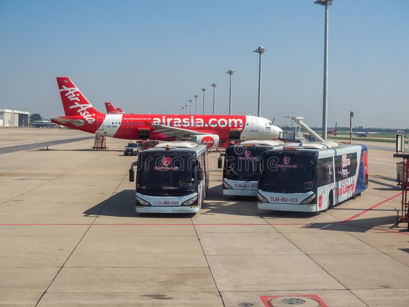 Flygplan- och för anslutningsbuss parkering nära landningsbanan i flygplats royaltyfri foto