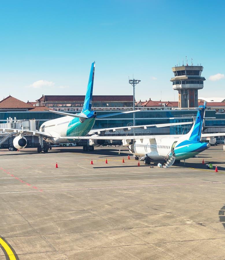 Flygplan och lastbil på landningsbanan i morgonsolljus, Denpasar flygplatsbyggnad, Bali, Indonesien royaltyfri bild