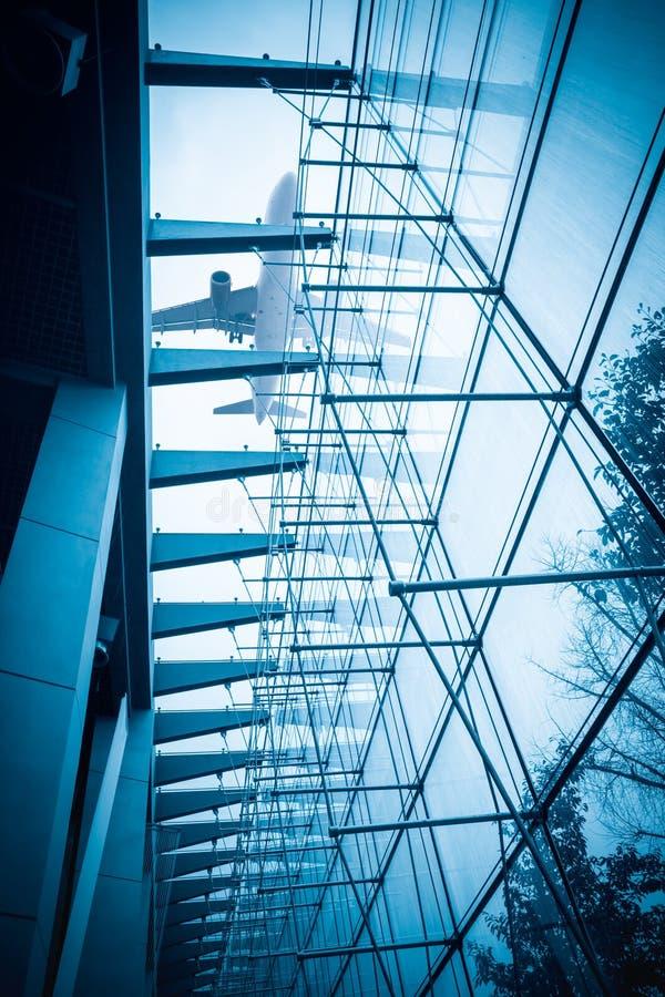 Flygplan ovanför den glass byggnaden arkivbild