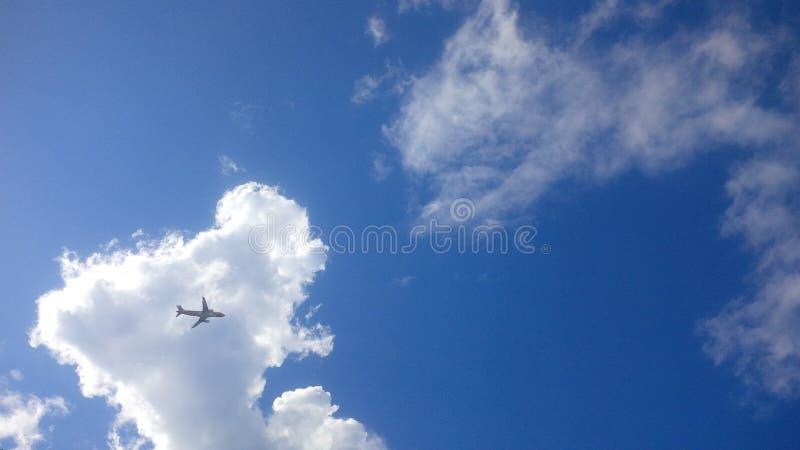 Flygplan på den molniga himlen arkivbilder