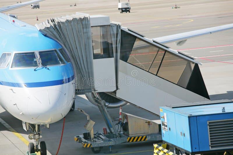 Flygplan på en flygplats med passagerarelandgången arkivfoto