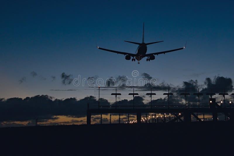 Flygplan på landning på aftonen fotografering för bildbyråer