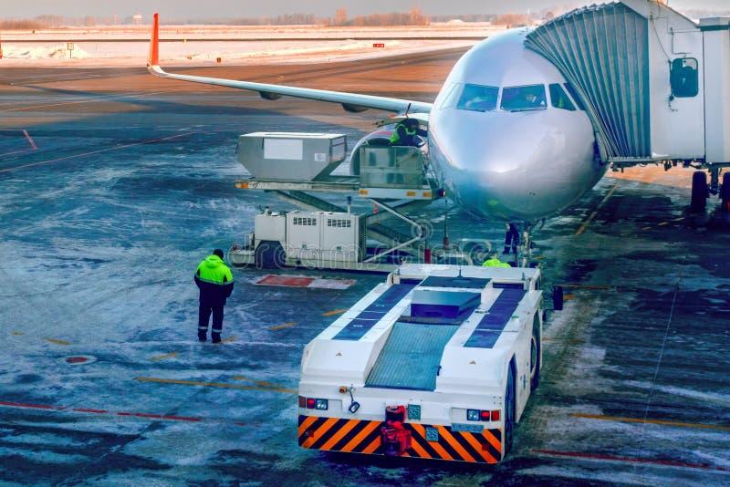 Flygplan som fästas till den jetway eller för passagerare teleskopiska landgången på flygplatsförklädet Förbereder sig för att st royaltyfri bild